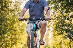 Sirva montar una bici en un parque en un día soleado hermoso imágenes de archivo libres de regalías
