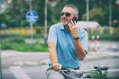 Sirva montar una bicicleta de la ciudad en estilo formal Foto de archivo