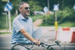 Sirva montar una bicicleta de la ciudad en estilo formal Imágenes de archivo libres de regalías