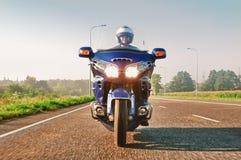 Sirva montar una motocicleta en un camino abierto Fotos de archivo