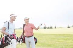 Sirva mostrar algo al amigo en el campo de golf contra el cielo claro foto de archivo libre de regalías