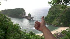 Sirva mostrar el pulgar para arriba en el backgroung hermoso del paisaje, playa de Atuh, cierre para arriba metrajes
