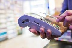 Sirva pagar con tecnología de NFC en tarjeta de crédito, en farmacia Imagenes de archivo