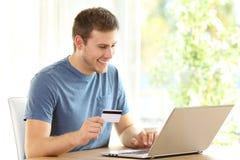 Sirva pagar en línea con la tarjeta de crédito y un ordenador portátil Fotografía de archivo libre de regalías
