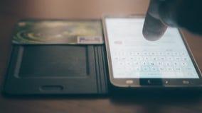 Sirva pagar en línea con la tarjeta y el smartphone de crédito Foco en el dedo almacen de video