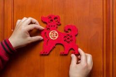 Sirva pegar un Año Nuevo chino del perro 2018 a la puerta Fotos de archivo