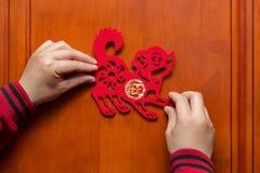 Sirva pegar un Año Nuevo chino del perro 2018 a la puerta Fotos de archivo libres de regalías