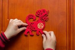 Sirva pegar un Año Nuevo chino del perro 2018 a una puerta Foto de archivo libre de regalías