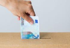 Sirva poner el dinero euro en la caja de la donación Foto de archivo libre de regalías