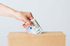 Sirva poner el dinero euro en la caja de la donación Fotografía de archivo