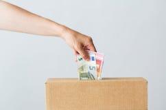 Sirva poner el dinero euro en la caja de la donación Fotos de archivo libres de regalías
