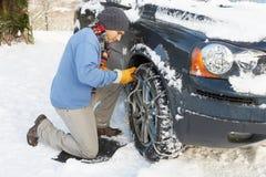 Sirva poner encadenamientos de nieve sobre el neumático del coche Fotos de archivo libres de regalías