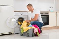 Sirva poner la ropa sucia en la lavadora Imagen de archivo libre de regalías