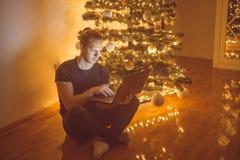Sirva sentarse al lado de árbol de los christmass y el trabajo en el ordenador portátil Imagen de archivo libre de regalías