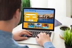 Sirva sentarse con el ordenador portátil con la reservación de hotel en la pantalla fotografía de archivo libre de regalías