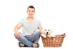 Sirva sentarse con un perrito lindo en el piso Foto de archivo libre de regalías