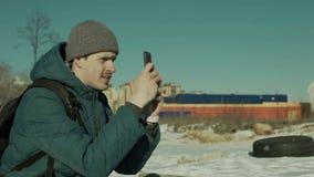 Sirva sentarse con un smartphone en las manos al aire libre almacen de video