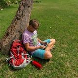 Sirva sentarse debajo del árbol y usar su tableta Foto de archivo libre de regalías