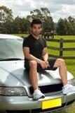 Sirva sentarse en capo del coche de plata en campo Imagen de archivo