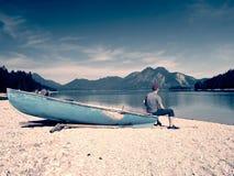 Sirva sentarse en el banco alpino del lago de la montaña en el barco anclado Foto de archivo