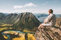 Sirva sentarse en el borde del acantilado que se relaja con paisaje aéreo de las montañas imagen de archivo