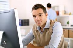 Sirva sentarse en el escritorio y el trabajo con el ordenador Imagen de archivo libre de regalías
