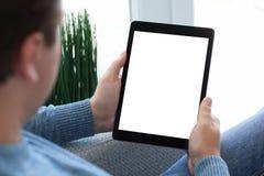 Sirva sentarse en el sofá que sostiene la tableta con la pantalla aislada fotografía de archivo libre de regalías
