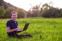 Sirva sentarse en hierba verde con el ordenador portátil y el trabajo Imagen de archivo