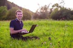 Sirva sentarse en hierba verde con el ordenador portátil y el trabajo Fotografía de archivo