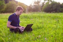 Sirva sentarse en hierba verde con el ordenador portátil y el trabajo Imagenes de archivo