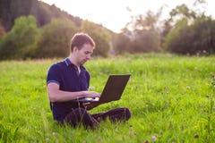 Sirva sentarse en hierba verde con el ordenador portátil y el trabajo Foto de archivo libre de regalías