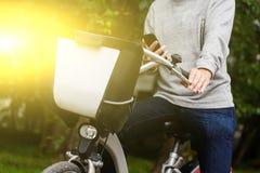 Sirva sentarse en la bici con el teléfono móvil en zona verde Foto de archivo