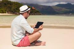 Sirva sentarse en la playa y la lectura en la tableta Fotos de archivo libres de regalías