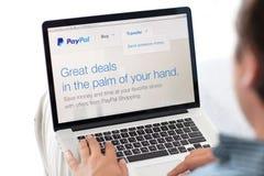 Sirva sentarse en la retina de MacBook con el sitio Paypal en la pantalla Imágenes de archivo libres de regalías