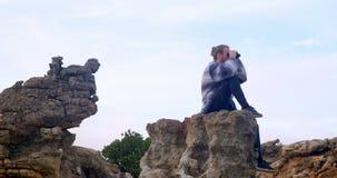 Sirva sentarse en la roca que mira a través de los prismáticos 4k almacen de video
