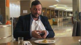 Sirva sentarse en la tabla en café y usar el teléfono móvil que fotografía la comida durante almuerzo almacen de video