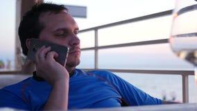 Sirva sentarse en la tabla en el café que habla en el teléfono HD, 4k, 3840x2160 almacen de metraje de vídeo