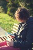 Sirva sentarse en parque del otoño en un banco, leyendo el libro electrónico y beba un poco de café Fotos de archivo libres de regalías