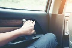 Sirva sentarse en puertas abiertas del coche y de coche de la mano del control foto de archivo libre de regalías