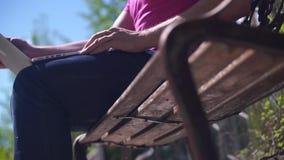 Sirva sentarse en un banco con un ordenador portátil, y después irá al aire libre almacen de metraje de vídeo