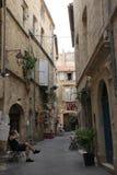 Sirva sentarse en un banco en una calle en la ciudad de Pezenas, Francia Imágenes de archivo libres de regalías