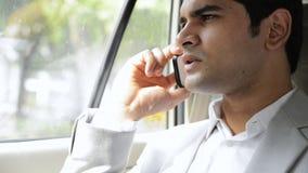 Sirva sentarse en un coche y hablar en un teléfono móvil almacen de metraje de vídeo
