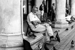 Sirva sentarse en un mercado en Cracovia y jugar con las palomas Fotografía de archivo