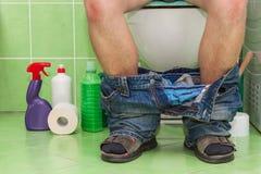 Sirva sentarse en un retrete en una casa de la familia Dolor abdominal diarrea imagen de archivo
