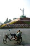 Sirva sentarse en una bici bajo la estatua de mao, China Fotografía de archivo