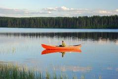 Sirva sentarse en una canoa roja en un lago en Finlandia en la puesta del sol Imágenes de archivo libres de regalías