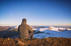 Sirva sentarse en una colina y mire al valle Imagen de archivo
