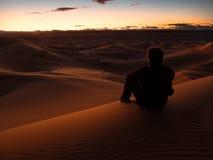 Sirva sentarse en una duna en el desierto mientras que mira la puesta del sol Fotos de archivo libres de regalías