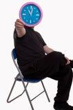 Sirva sentarse en una silla y sostener delante de su cara un reloj de pared grande que muestra tiempo Imagenes de archivo