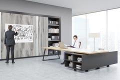Sirva sentarse en una tabla masiva del CEO, su colega está dibujando imagenes de archivo